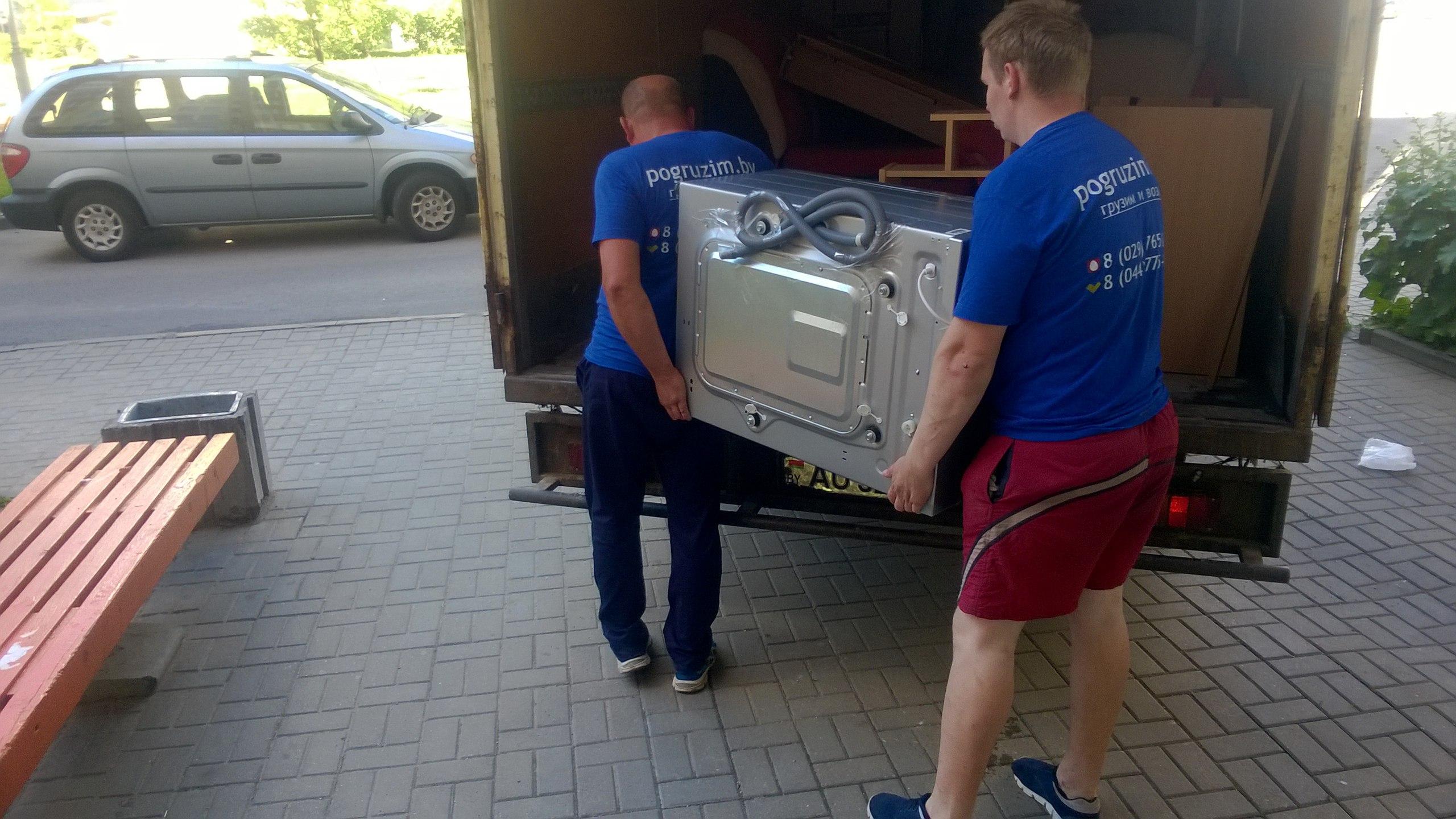 грузчики несут стиральную машину