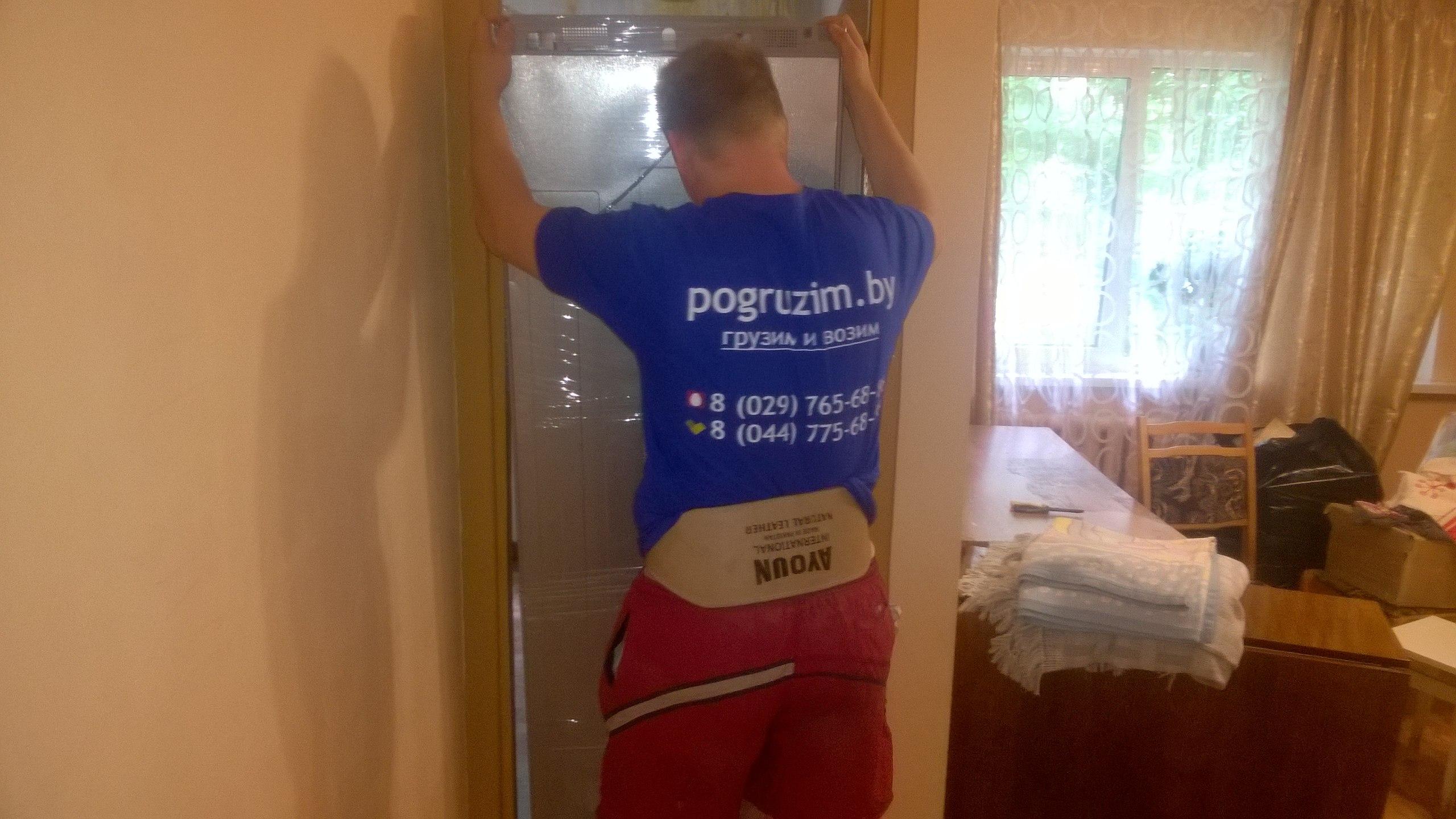 грузчик заносит холодильник в дом