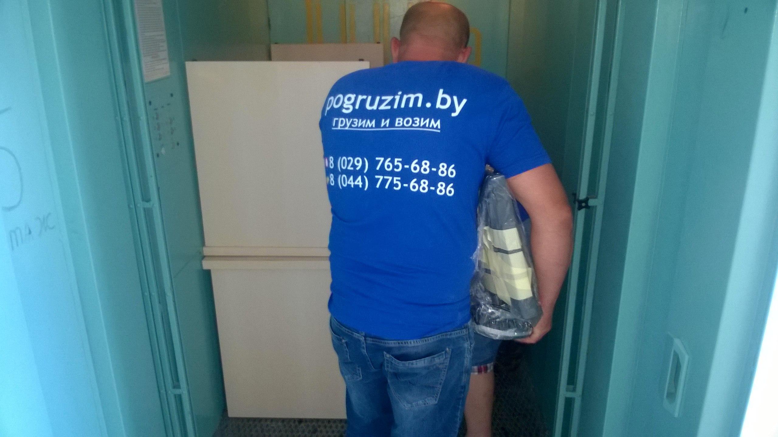 Грузчик переносит вещи в лифт